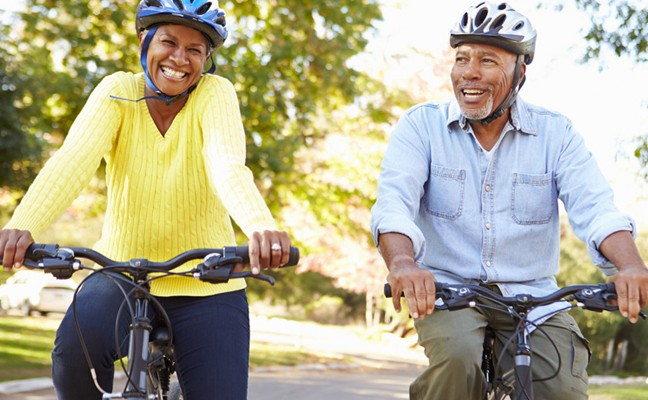 Older African American man and woman riding bikes and wearing helmets