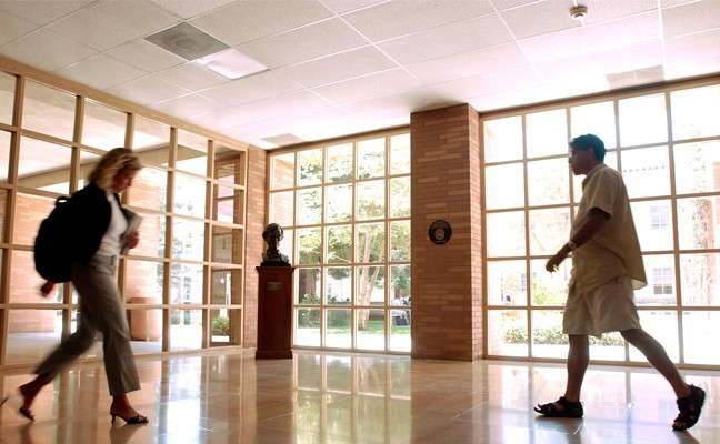 School of Law interior, with a man and a woman walking through a lobby