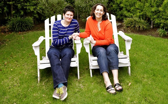 Two women sitting in adjacent chairs and holding hands
