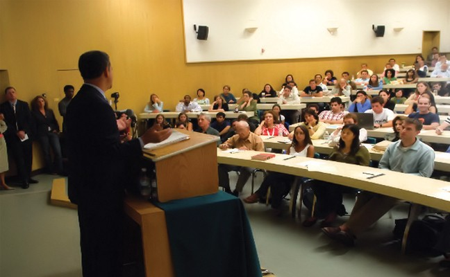 Speaker at podium, with students listening from desks