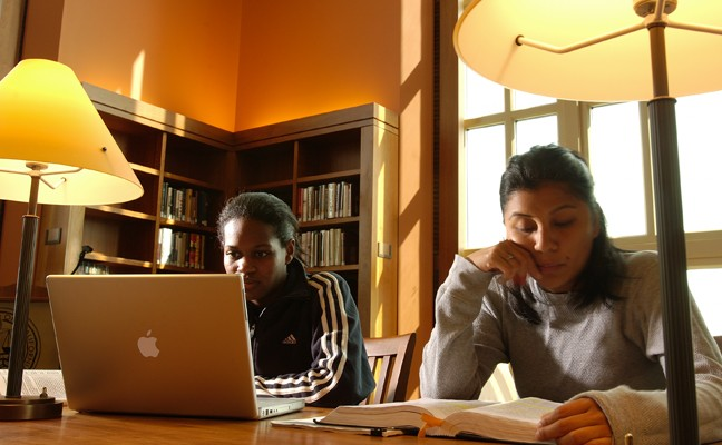 Two students using books and a laptop to study in the library