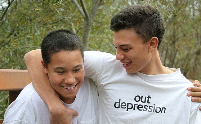 "Two young men in t-shirts, one of which says ""Out Depression"""