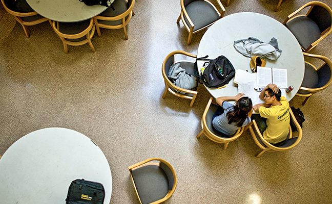 aerial shot of two students with books and backpacks studying at table in common area