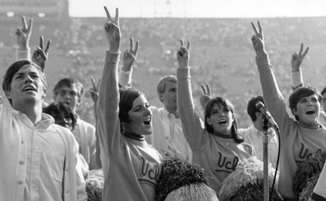 Male and female Spirit Squad members cheer at a 1968 football game