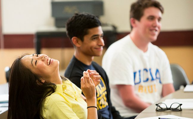 Three students--one female, two male--smile and laugh in response to a lecture