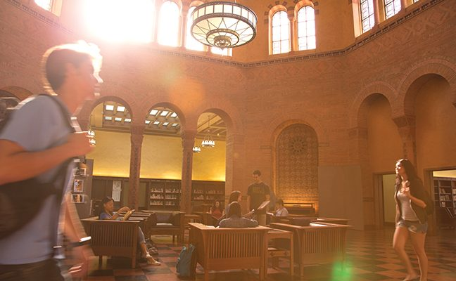 Students in the Powell Library rotunda, with sunlight streaming through the upper windows