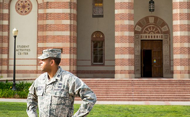 A man wearing an Airman Battle Uniform stands in front of the Student Activities Center.