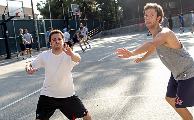 Two male students play basketball on an outdoor court, with other games in the background.