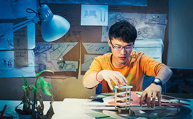 Male student at desk working with design model, with schematics posted behind him