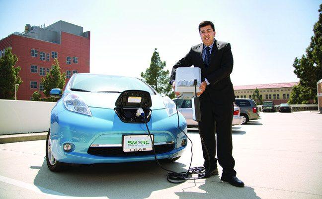 UCLA professor Rajit Gadh holding prototype battery plugged into car
