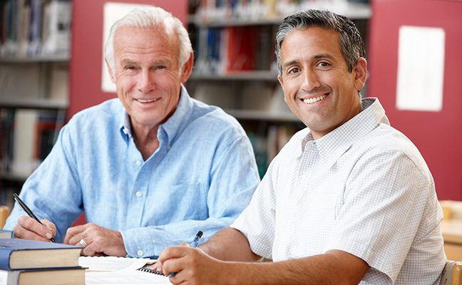 Two older men studying in common area