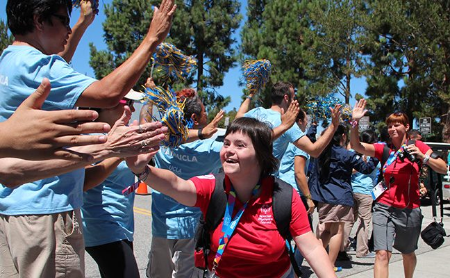 Volunteers welcome participants of the Special Olympics World Games.