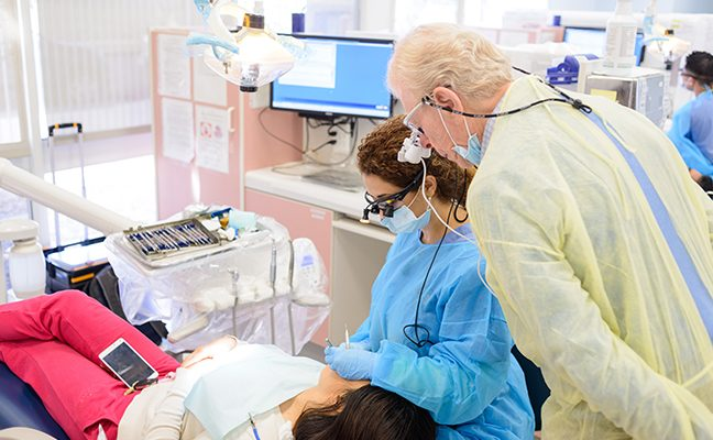 Instructor observing student dentist with patient