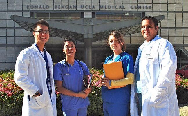Two men in white coats and two women in scrubs in front of the Ronald Reagan UCLA Medical Center