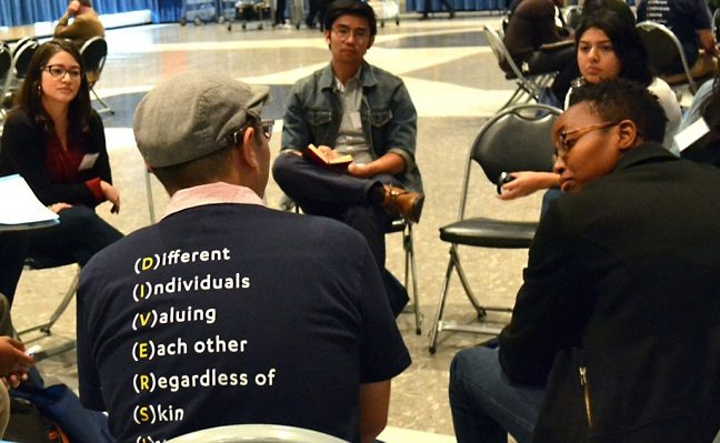 Students sitting on chairs in a circle discuss public policy reforms.
