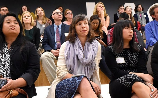 Audience members listening to a research presentation in an auditorium