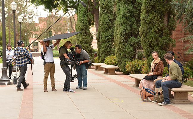 Students film a scene with actors on campus.