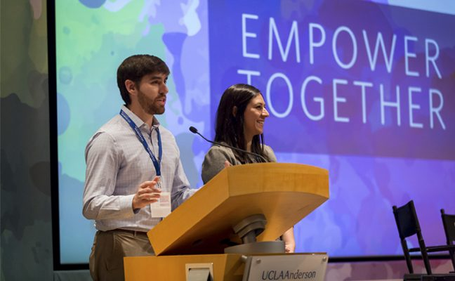 Two students--one male and one female--stand at a podium during a presentation.