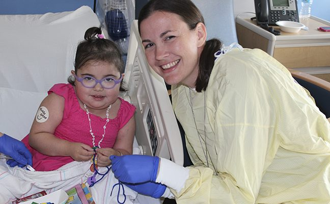 young female patient in hospital bed and nurse work together on a craft project