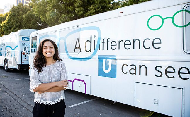 A student stands in front of a UCLA Mobile Eye Clinic van.