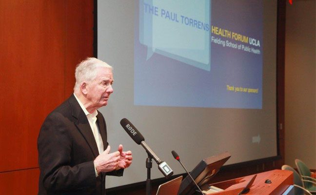 Dr. Paul Torrens in front of a microphone at a Paul Torrens Health Forum.