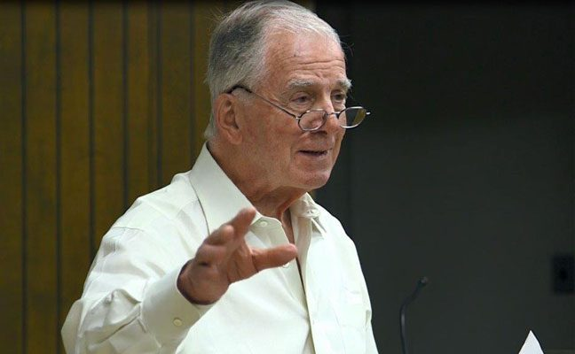 Dr. Paul Torres speaking to a class, with a sheet of notes in his hand.
