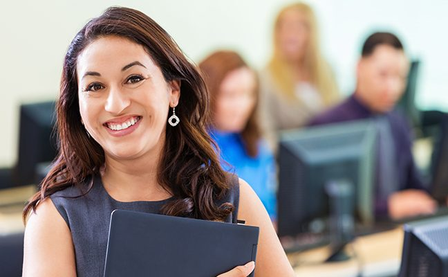 A female student clutches a notebook while smiling at the camera.