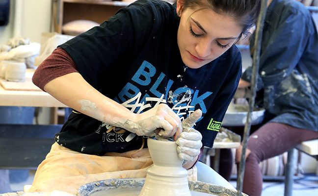 Young woman molds pottery with her hands in art studio.