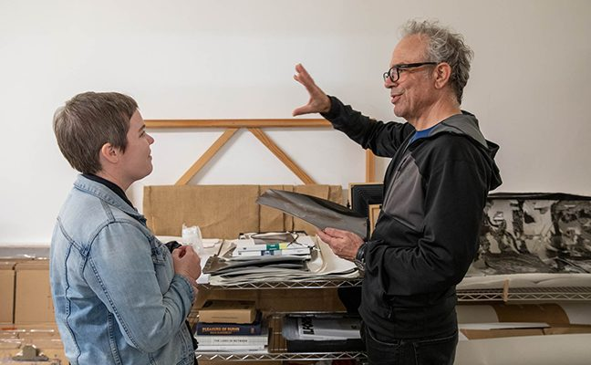 Professor gestures to student in art studio while holding a canvas swatch.