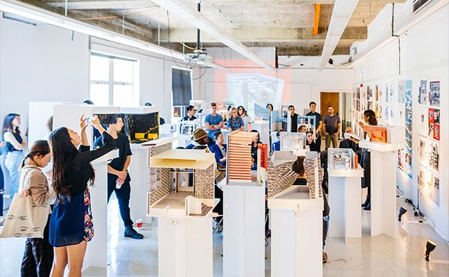 Large group of students gather in exhibit space filled with dioramas in open exhibit space.