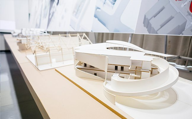 Close-up of long table filled with small, white architectural models.
