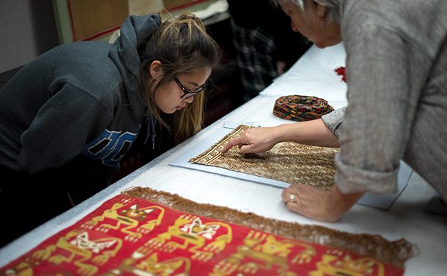 Student and professor closely examine textiles from around the world.