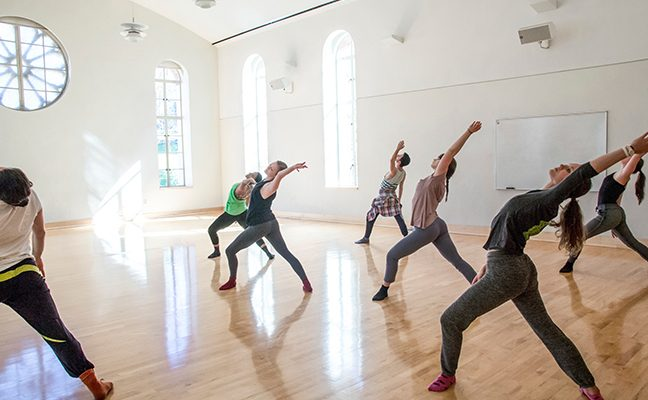 Group of dance students practice choreography in brightly lit studio space.