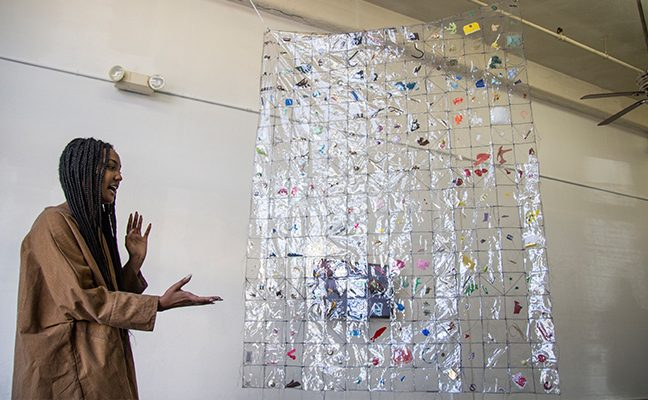 Student artist gesturing to hanging plastic cross-cultural textile art piece.