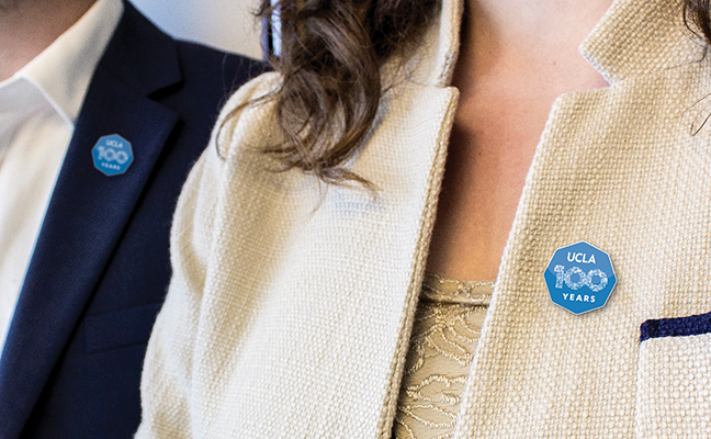 Close up of a man and a woman wearing pins on their jacket lapels.